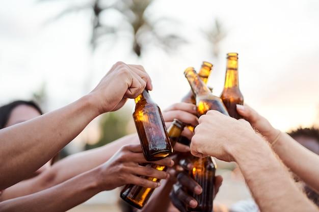 Gros plan sur les mains d'un groupe d'amis acclamant avec de la bière à l'extérieur du concept d'amis d'été soleil...