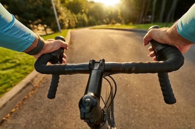 Gros plan des mains sur le guidon d'un cycliste professionnel faisant du vélo de route dans le parc.