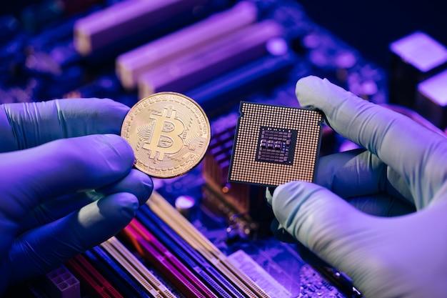 Gros plan des mains d'homme d'affaires détiennent bitcoin or et cpu sur la carte mère