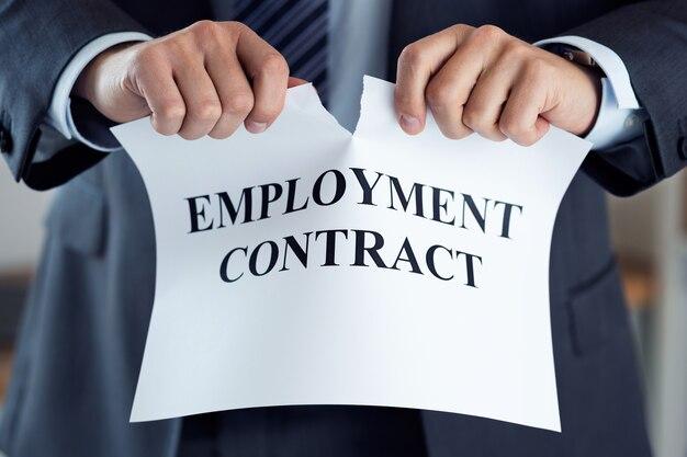 Gros plan des mains d'homme d'affaires rompant le contrat de travail