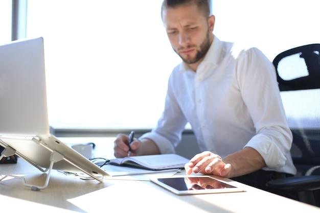 Gros plan sur les mains d'un homme d'affaires touchant une tablette, multitâche à l'écran dans un bureau.