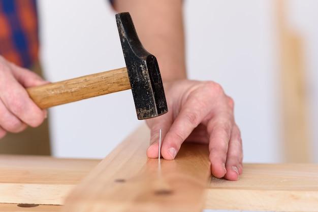 Gros plan des mains d'un homme à l'aide d'un marteau et d'un clou sur un bois