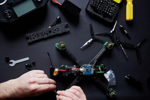 Gros plan des mains de l'homme assembler un drone fpv à partir de pièces, à l'aide d'outils, préparer un quadcopter de course à grande vitesse pour le vol. réparez le drone avant le processus de formation.