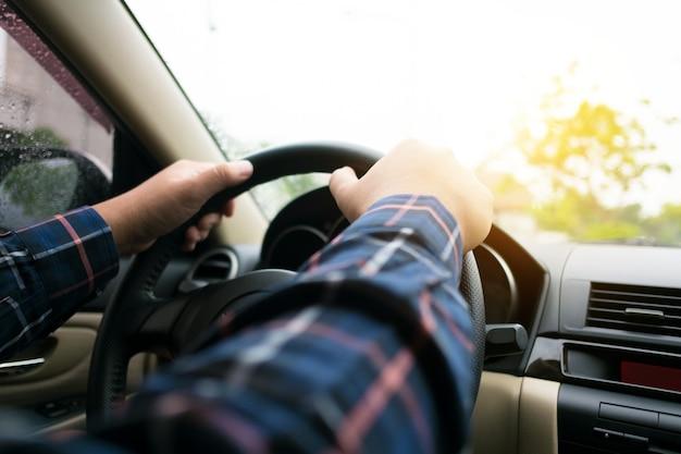 Gros plan des mains de l'homme au volant d'une voiture