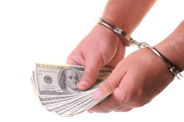 Gros plan des mains de l'homme dans des menottes métalliques fermées comptant des dollars américains en espèces