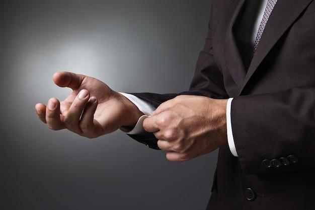 Gros plan des mains de l'homme élégance avec bouton de manchette sur fond sombre