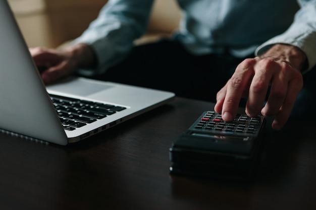 Gros plan des mains d'un homme faisant des factures et travaillant à domicile