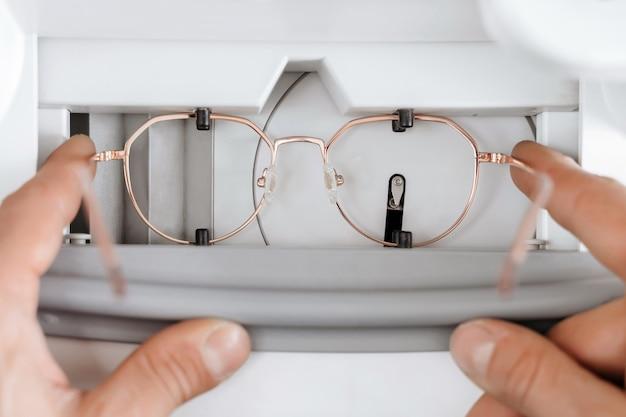 Gros plan des mains de l'homme faisant monture de lunettes individuelles en atelier d'opticien