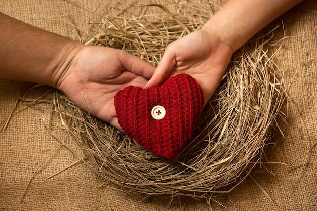 Gros plan sur des mains d'homme et de femme tenant un coeur rouge décoratif dans un nid