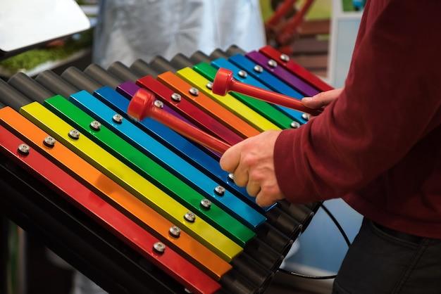 Gros plan des mains de l'homme jouant au vibraphone.