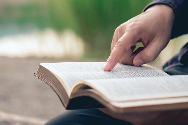 Gros plan des mains de l'homme lors de la lecture de la bible à l'extérieur des lectures de l'éducation biblique