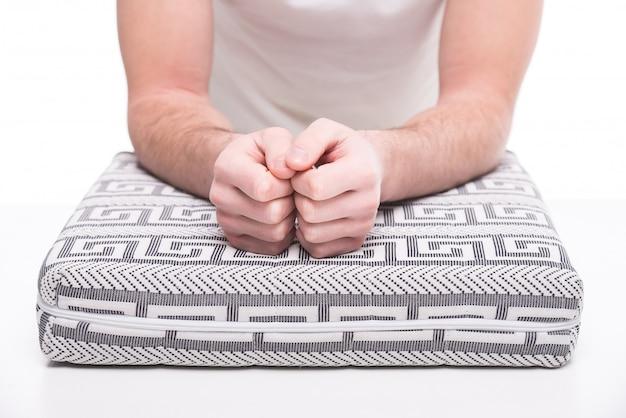 Gros plan des mains de l'homme sur le matelas orthopédique.