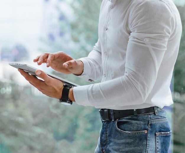 Gros plan des mains de l'homme qui utilise un tablet pc indoor