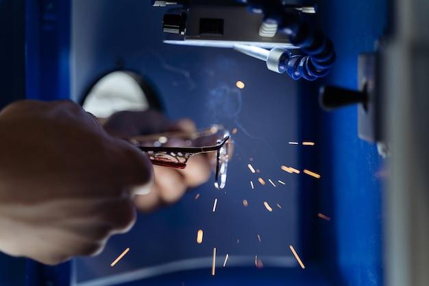Gros plan des mains de l'homme réparant le cadre de lunettes avec machine de soudage laser en atelier d'optique