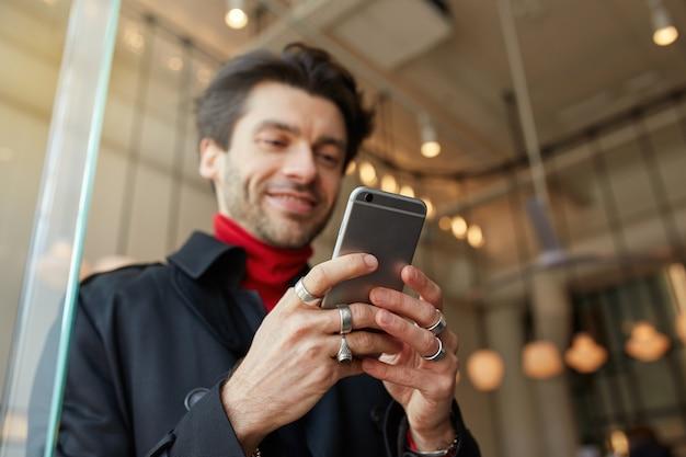 Gros plan des mains de l'homme soulevées avec des anneaux gardant le téléphone portable tout en posant sur fond de café de la ville, message texte à des amis et souriant légèrement tout en regardant positivement sur l'écran