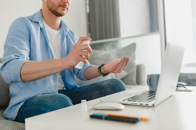 Gros plan sur les mains de l'homme spray désinfectant antiseptique sur le lieu de travail à la maison travaillant en ligne sur un ordinateur portable