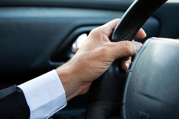 Gros plan sur les mains d'un homme tenant le volant pendant la conduite d'une voiture. homme d'affaires au volant, recadré. la main du conducteur sur le volant en costume. guy est assis dans la voiture et tient les mains sur le volant