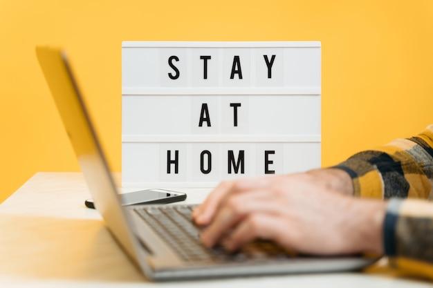 Gros plan des mains de l'homme travaillant à distance avec un ordinateur portable pendant la quarantaine en raison d'une épidémie de coronavirus.