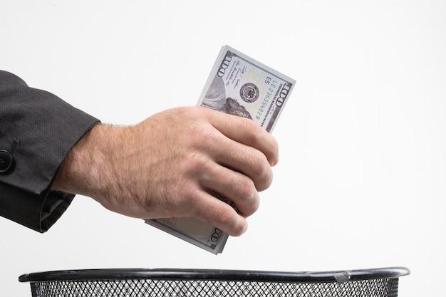 Gros plan des mains des hommes jetant de l'argent à la poubelle