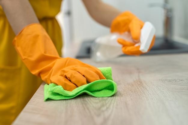 Gros plan sur des mains humaines dans des gants jaunes avec une surface en bois de nettoyage par pulvérisation