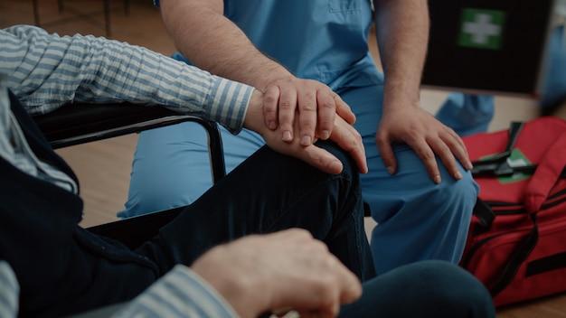 Gros plan des mains de l'infirmière et du patient senior lors d'une visite médicale