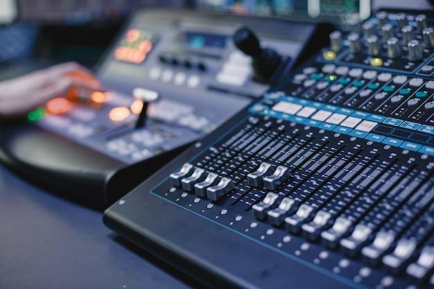 Gros plan des mains de l'ingénieur du son enregistrant de la musique