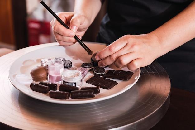 Gros plan des mains d'un jeune chef pâtissier faisant des chocolats
