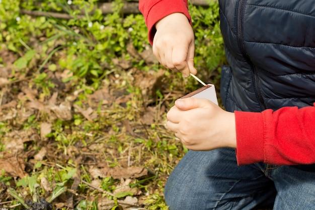 Gros plan sur les mains d'un jeune enfant agenouillé au sol frappant une allumette sur une boîte