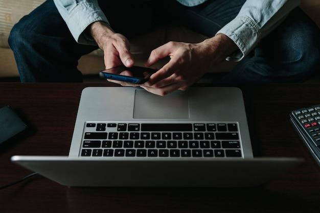 Gros plan des mains d'un jeune entrepreneur à l'aide d'un téléphone tout en travaillant à domicile