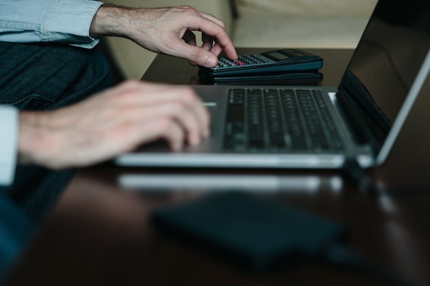 Gros plan des mains d'un jeune entrepreneur établissant des factures et travaillant à domicile