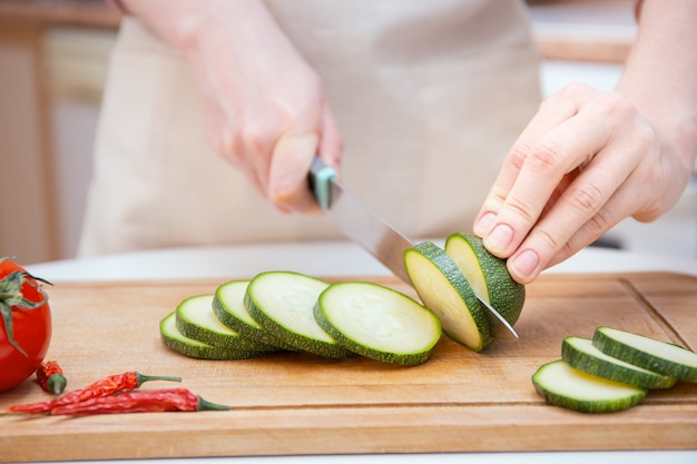 Gros plan mains d'une jeune femme coupées avec un couteau en tranches ou en tranches de jeune concombre courgette sur une planche à découper en bois. préparation des ingrédients et des légumes avant la cuisson et pour les grillades.