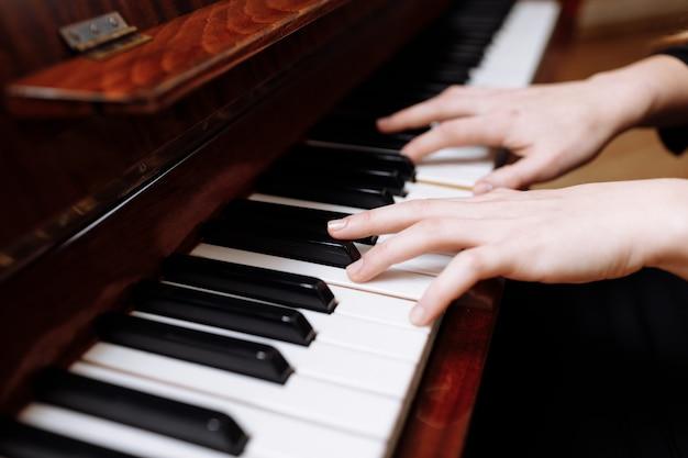 Gros plan des mains d'une jeune femme jouant du piano.