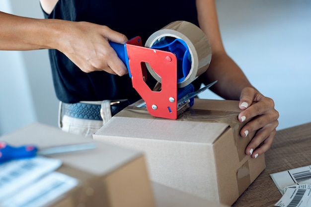 Gros plan sur des mains de jeune femme tenant une machine à emballer et scellant des boîtes en carton avec du ruban adhésif pour livrer les produits commandés en ligne aux clients de sa petite entreprise en démarrage.