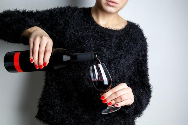 Gros plan des mains d'une jeune femme versant du vin rouge