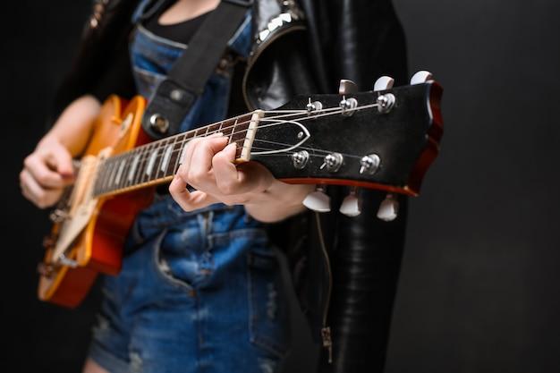 Gros plan des mains de la jeune fille à la guitare sur fond noir.