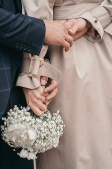 Gros plan des mains des jeunes mariés, la mariée tient un bouquet de mariage bouquet de mariée de pivoines et de gypsophile