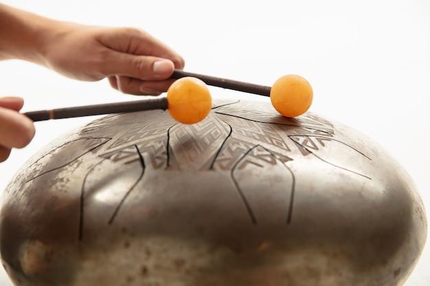 Un gros plan des mains jouant du tambour hank sur fond de studio blanc