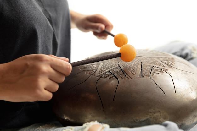 Un gros plan des mains jouant du tambour hank sur le mur blanc du studio.
