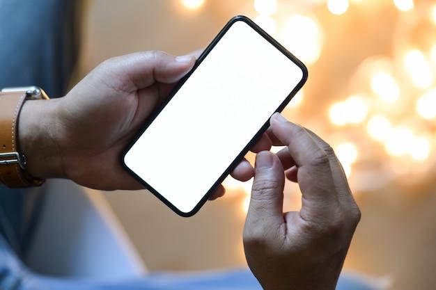 Gros plan des mains mâles à l'aide de smartphone mobile à l'arrière-plan flou de la nuit.