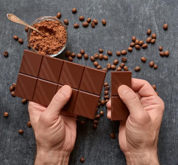 Gros plan des mains mâles brisant une barre de chocolat