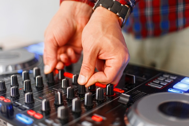 Gros plan des mains mâles du dj travaillant sur la console de mixage
