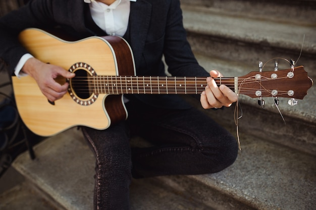 Gros plan des mains mâles jouant de la guitare acoustique dans les escaliers