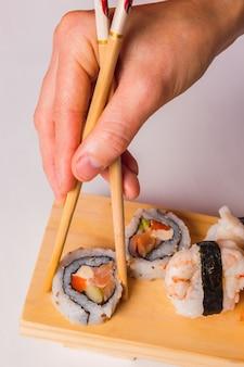 Gros plan des mains mangeant des sushis avec des baguettes.