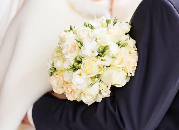 Gros plan des mains de mariée tenant beau bouquet de mariage d'hiver.