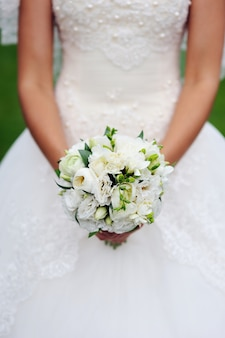 Gros plan des mains de la mariée tenant le beau bouquet de mariée