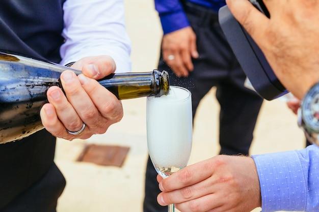 Gros plan des mains des mariés avec des lunettes champagne
