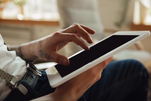 Gros plan des mains masculines à l'aide d'une tablette avec écran vide, fond.