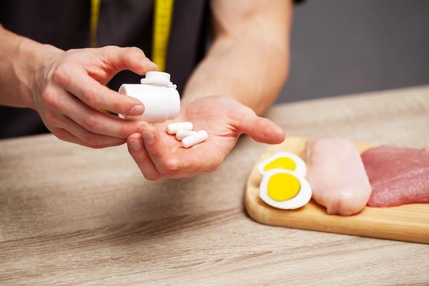 Gros plan des mains masculines avec des aliments riches en protéines sur une planche à découper et des comprimés sur la table