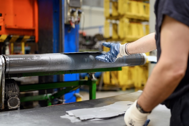 Gros plan sur des mains masculines dans des gants de travail travaillant dans une usine de transformation des métaux. travailleur utilisant des machines dans l'industrie sidérurgique, la fabrication, la production.