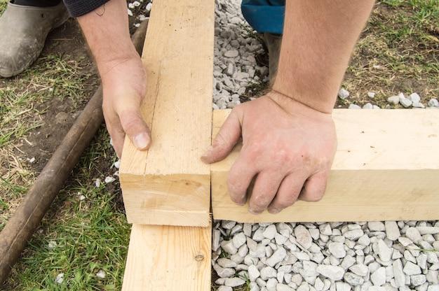 Gros plan sur des mains masculines rugueuses utilisant du nouveau bois pour le travail, à l'extérieur.